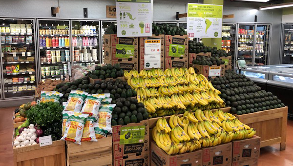 A display of avocados and bananas at a grocery store