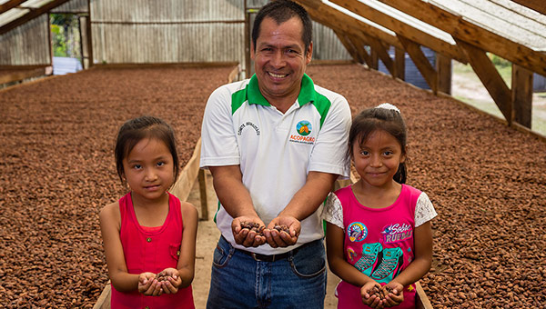 Farmer and children with cocoa beans