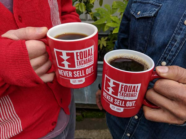 two people holding red coffee mugs