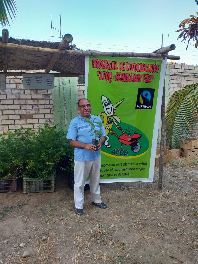 Banana farmer in front of APOQ banner
