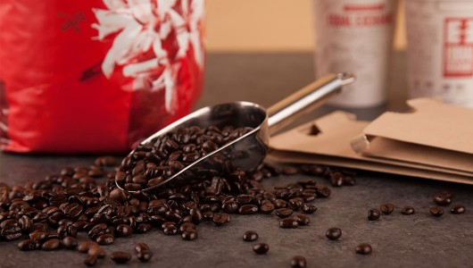 Scoop of coffee beans with a coffee bag and cups in the background