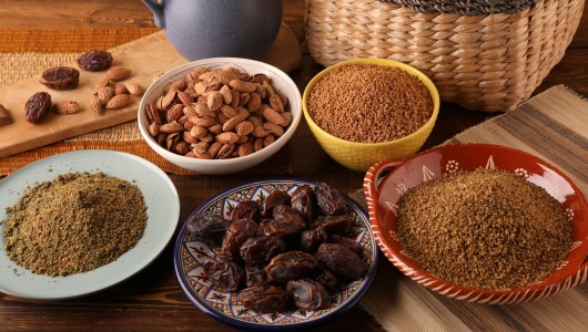 Bowls of Palestinian products including freekeh, maftoul and dates