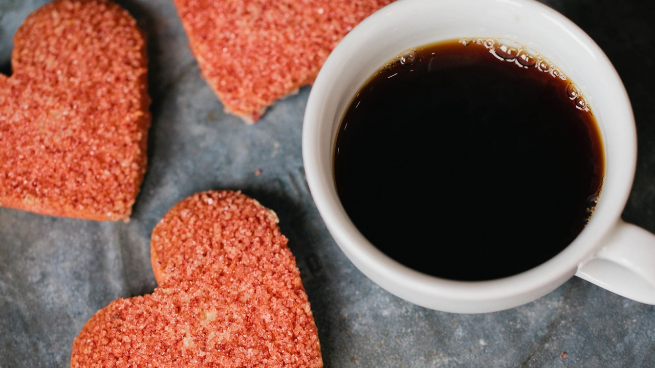 Mug of coffee with heart-shaped cookies