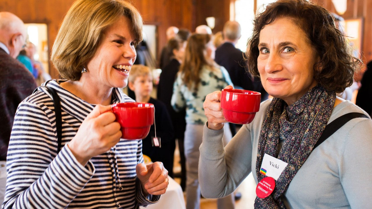 Two women drinking organic coffee in a crowded room