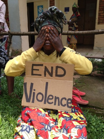 "Woman kneeling with a sign in her lap that says ""End Violence"", and her hands covering her eyes."