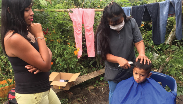 Flor Maria Bueno and assistant cutting a child's hair at the hair salon at her home.